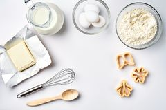 Objects and ingredients for baking, plastic molds for cookies on a white background. Flour, eggs, whisk, milk, butter. Cream. Top view, space for text. Still Royalty Free Stock Images