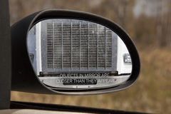 Objects in Mirror are closer than they Appear. Looking through the rear view mirror you see the front grill of a large truck, obviously too close for comfort royalty free stock image