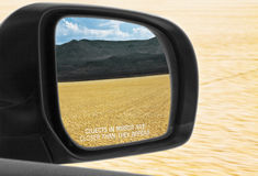Objects In Mirror Are Closer Than They Appear Desert. While driving on a desert playa a look into the side mirror reveals the desert being left behind while the Royalty Free Stock Photos
