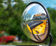 Objects in Mirror May Appear Larger. School Bus reflected in own side mirror stock photo