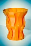 Objects printed by 3d printer. Bright colorful object. Vase orange color. Automatic three dimensional performs plastic modeling. Modern 3D printing technology royalty free stock photography