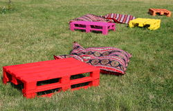 Objects for rest on the grass. Colorful wooden pieces and pillows Stock Photography