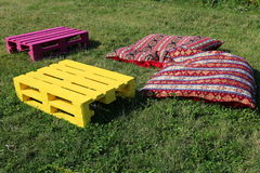 Objects for rest on the grass. Colorful wooden pieces and pillows Stock Photo
