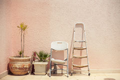Objects standing in a row. Mainstream fashion photo. Objects standing in a row stepladder chair pot on wall background Stock Photography