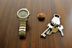 Objects on the table. Watch, Coins and Keys over a wood table Stock Photos