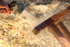 Objects: Teak wood table being refinished, man spraying Stock Image