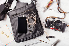 Objects on wooden background: leather bag, camera, smartphone. Keys, knife. Outfit of young man Royalty Free Stock Images
