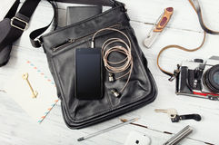Objects on wooden background: leather bag, camera, smartphone. Keys, knife. Outfit of young man Royalty Free Stock Photography