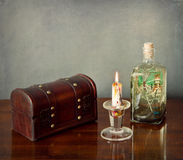 Interior still life: wooden chest,candle,glass bottle Stock Images