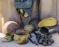 Objekt av det stora patriotiska kriget Hjälm hörlurar med mikrofon, kastare, exponeringsglas, kopp, fältlock, kantin, ammunition, Royaltyfria Foton