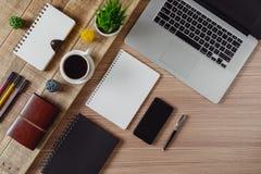 Objekt, bärbar dator och kaffe för kontorstillförsel på lantligt trä arkivfoton