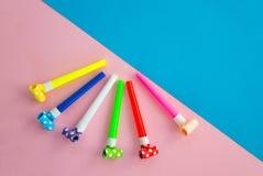 Objekt f?r att fira en f?delsedagl?gn p? bl?tt och en rosa bakgrund Ballonger, r?r f?r coctailar och r?r, visslingar och arkivfoto
