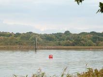 Objet de rouge du numéro 32 de balise de mer dans la côte de rivière de courant de mer Images libres de droits