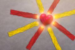 objet rouge de coeur avec les étiquettes de papier rouges et jaunes Photos stock