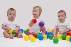 Objetivas triplas engraçadas do bebê que smiliing e que jogam com bolas coloridas Tiro do estúdio Fotos de Stock Royalty Free