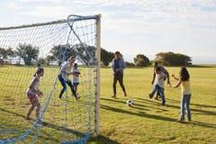 Objetivo de defesa da menina durante o jogo de futebol da família imagem de stock royalty free