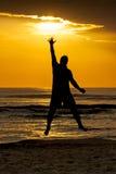 Objetivo de salto de Sun do toque do mar do homem da silhueta Imagens de Stock Royalty Free