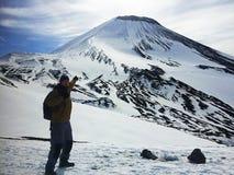 Objetivo seguinte: uma pessoa está no lado de um vulcão e de pontos à parte superior fotos de stock royalty free
