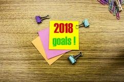 2018 objetivos na nota pegajosa amarela, no fundo de madeira Conceito das definições do ano novo Foto de Stock