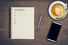 2018 OBJETIVOS no livro, no café e no telefone de nota do papel vazio na madeira Ta Imagens de Stock