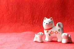 Objeto japonés del perro del Año Nuevo en fondo de papel rojo Fotografía de archivo