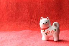 Objeto japonés del perro del Año Nuevo en fondo de papel rojo Imágenes de archivo libres de regalías