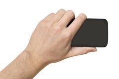 Objeto negro en el fondo del blanco de la mano del hombre Imagen de archivo libre de regalías