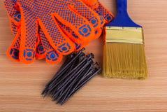 Objetos da construção no fundo de madeira: escova, luvas e n de pintura Fotografia de Stock Royalty Free