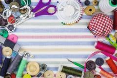 Objetos de costura coloridos em um fundo da tela imagens de stock