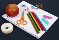 objetos de la Detrás-a-escuela en el cuaderno espiral Fotografía de archivo libre de regalías