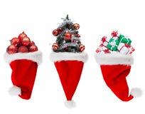 Objetos de la Navidad en los sombreros de santa Fotos de archivo