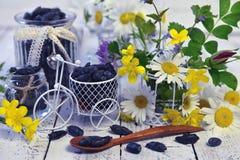 Objetos del vintage, cuchara con la baya de la madreselva y flores amarillas en la tabla Fotografía de archivo