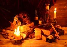 Objetos mágicos de los brujos en luz de una vela Imagenes de archivo