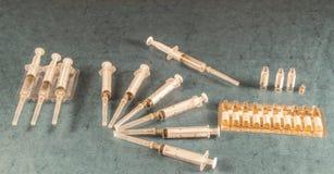 Objetos médicos em um fundo azul Seringas e ampolas Fotos de Stock Royalty Free