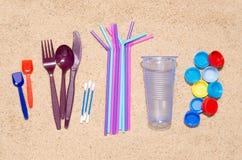 Objetos plásticos que causam a poluição do ambiente, especialmente oceanos do único uso descartável Vista superior na areia fotografia de stock