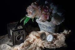 Objetos retros de la cámara de caja, del reloj del mando y de flores foto de archivo libre de regalías