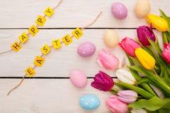 Objetos tradicionales de Pascua en la enhorabuena feliz de pascua del fondo de madera imagen de archivo