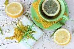 Objetos y elementos verdes y amarillos de la decoración: taza de té, caja de regalo, flores salvajes, manzana, hojas secas en un  Fotos de archivo