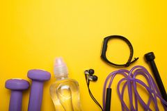 Objets femelles de sports sur un fond jaune Haltères, une bouteille de l'eau, écouteurs, une corde de saut et un bracelet de form images stock