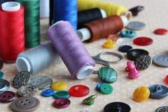 Objets pour la couture : boutons en plastique, fil coloré et scis Images stock