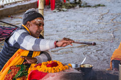 Oblaciones de ofrecimiento de un sacerdote hindú en el fuego en el Kumbha Mela en la India foto de archivo libre de regalías