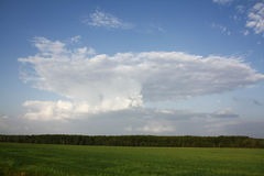 Oblako. A beautiful cloud in the blue sky and the green fields and forests Royalty Free Stock Photography