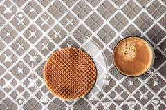 Oblea con la taza de café en el fondo del alivio horizontal Foto de archivo libre de regalías