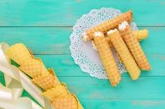 Obleas blandas de la miel bajo la forma de tubos, rellenos con crema del aire en la servilleta blanca del cordón Foto de archivo libre de regalías