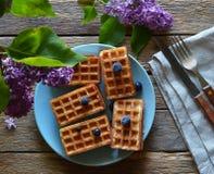 Obleas con los arándanos y las lilas en una tabla de madera Foto de archivo