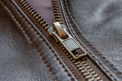 Oblique close up of the zip of an elegant brown leather jacket. There is a double stitching on both sides of the zipper Royalty Free Stock Images