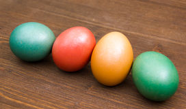Oblique row of colorful eggs on wood Stock Photo