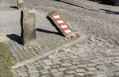 Oblique stone on the roadside. With warning stripes stock photos