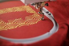 Oblique view on embroidery of traditional shell pattern framing pig outline with gold on red fabric - chinese new year concept stock image