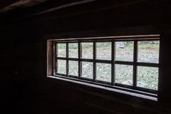 Oblique view looking out the window of an old log cabin. Horizontal aspect Royalty Free Stock Photography